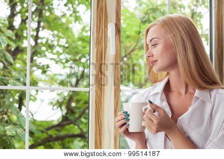 Pretty blond girl is relaxing on windowsill