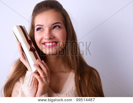 Young woman happy smile hold gift box in hands,standing over gray background