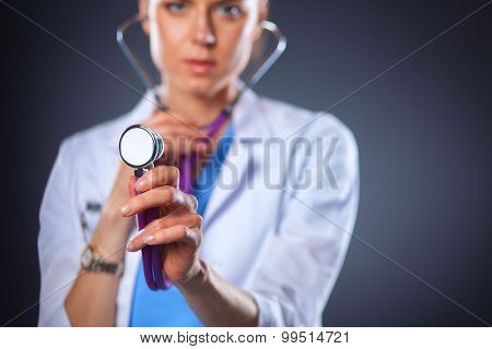 Female doctor with a stethoscope listening, isolated on grey background