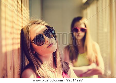 Two sad  teenage girls wearing sunglasses in sunroom with blinds