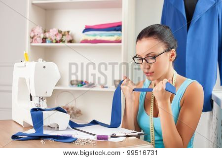 Cheerful young clothes designer is in process of work