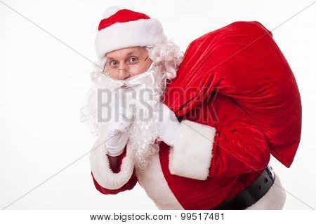 Cheerful Santa Claus is carrying presents secretly