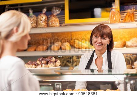 Cheerful saleswoman is serving a customer in bakery