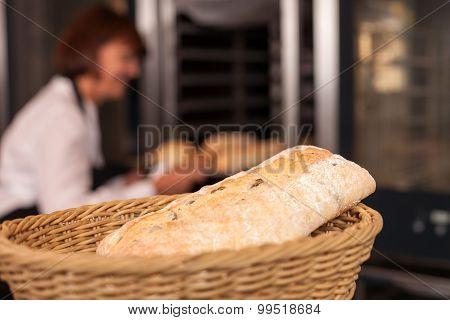 Skilled female baker is working in bakehouse