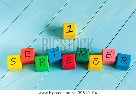 First September sign on color wooden cubes with light blue wood background. Back to school time