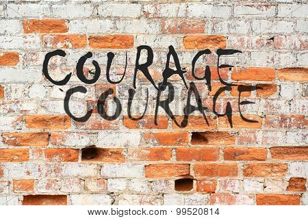 Courage message on brick wall