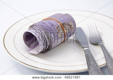 Conceptual composition, white plate full of malaysia money.