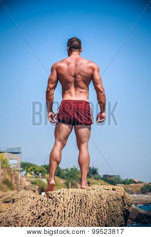 Man Athlete stands on a rock by the sea against the sky