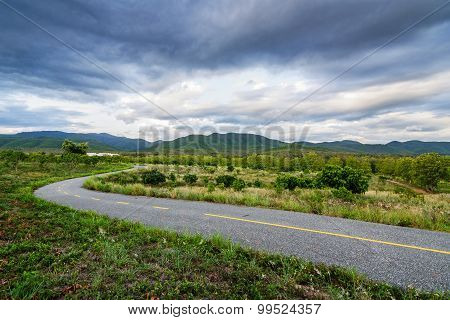 Road running through green hills in rainny season.Thailand.