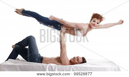 Funny young people perform acrobatic stunt in bed