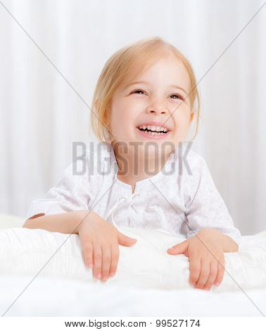 happy little girl on a bed