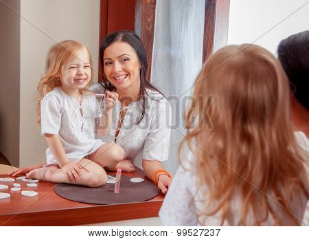 Mother and daughter in room interior near mirror