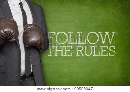 Follow the rules on blackboard with businessman on side
