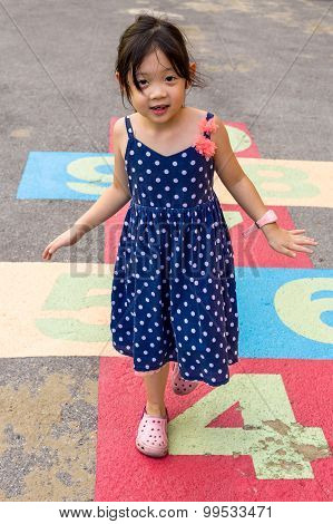 Child Playing Hopscotch / Child Playing Hopscotch On Playground