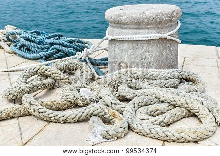Old Stone Mooring On A Stone Paved Pier
