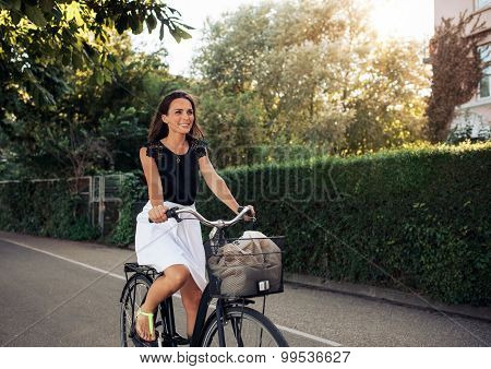 Beautiful Young Woman Cycling Along Street