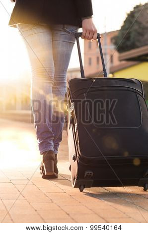 Woman wheeling suitcase on railway station platform