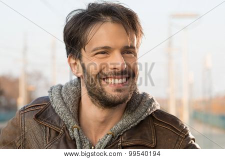 Closeup of smiling man looking away outside