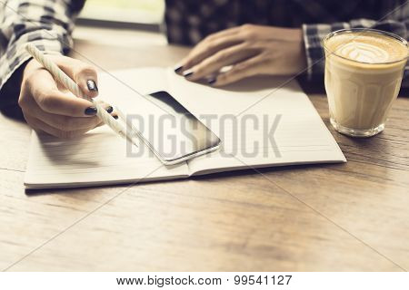 Girl With Cell Phone, Diary And Cup Of Coffee At The Wooden Table