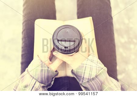 Girl Sitting On The Floor With A Cup Of Coffee And A Book