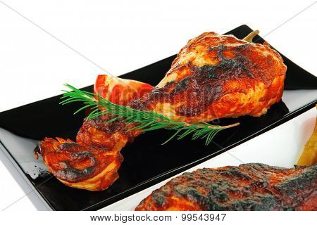 fresh grilled drumstick on plates with vegetables
