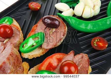 snakes on black grill plate : tartlets with sliced meat isolated over white background