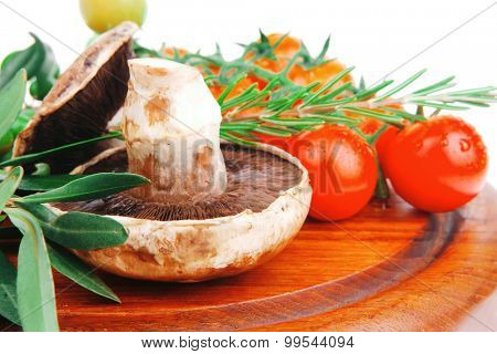 raw vegetables on dark wood plate over white