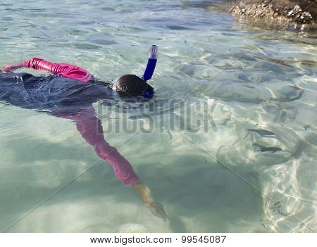 Girl reaches for fish while snorkelling