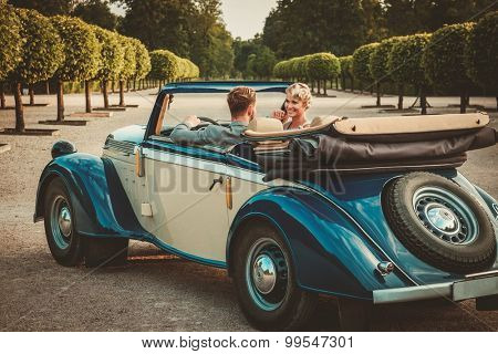 Wealthy couple in classic convertible