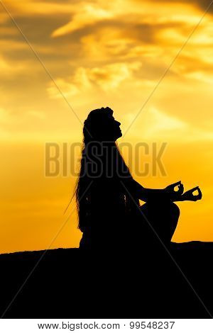 Woman meditating in a yoga pose outdoor