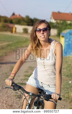 Portrait Of A Happy Brunette Girl Riding Bicycle On The Clay Running Track
