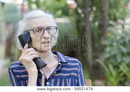 Old Lady Talking On The Phone In The Backyard