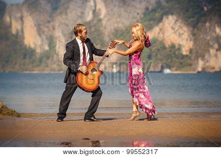 Dancing Blonde Back-view And Guitarist On Beach