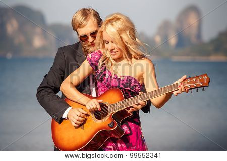 Blonde Girl With Guitar By Guitarist On Beach