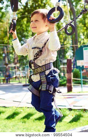little boy having fun in rope park