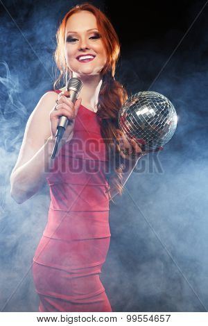 Young happy girl singing into microphone at party