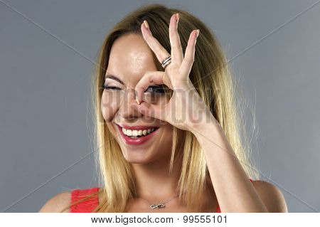 Young Woman With Ok Sign On Her Eye