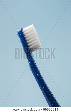 Blue toothbrush covered with water drops