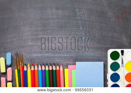 School supplies on blackboard background. Top view with copy space