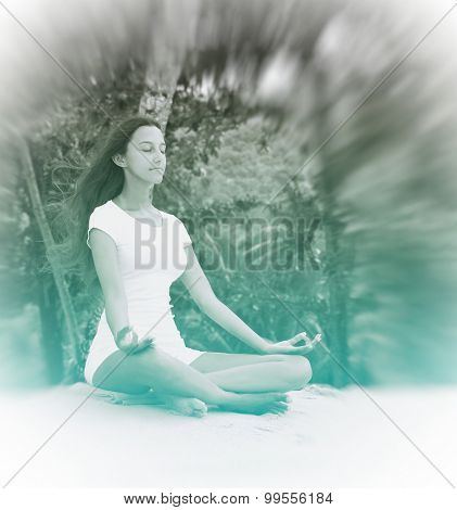 Healthy Young Woman Relaxing at the Beach with Yoga Activity. Captured on White Sand with Trees at the Background.