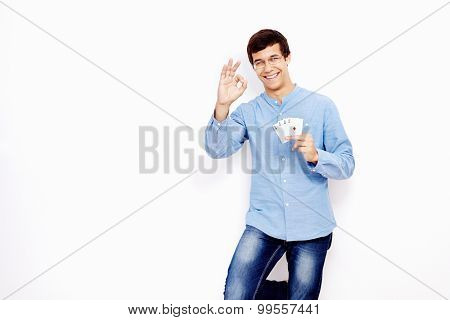 Young hispanic man wearing jeans and glasses holding four aces (spades, hearts, clubs and diamonds) in his hand and showing A-ok hand gesture with smile against white wall - gambling concept