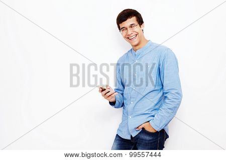 Young hispanic man wearing jeans and glasses holding smartphone in his hand and smiling against white wall - communication concept