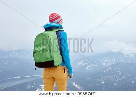 Back view of young woman wearing pink hat, blue jacket, green backpack and yellow pants standing against winter mountains - adventure concept