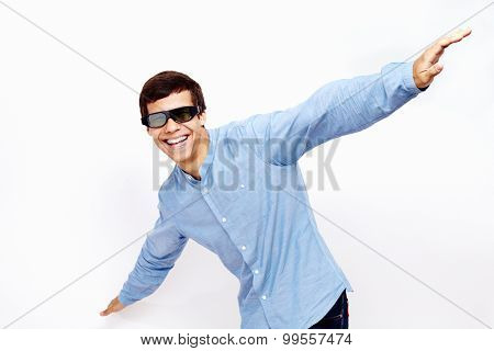 Young hispanic man wearing jeans shirt and 3D TV LCD shutter glasses laughing and having fun with hands outstretched lifted upwards against white wall - 3D film concept