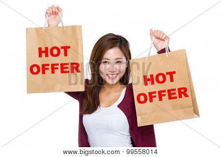 Asian woman raise up the shopping bag for showing hot offer