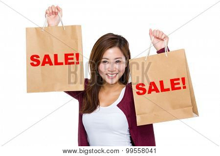 Asian woman raise up the shopping bag for showing a word sale!
