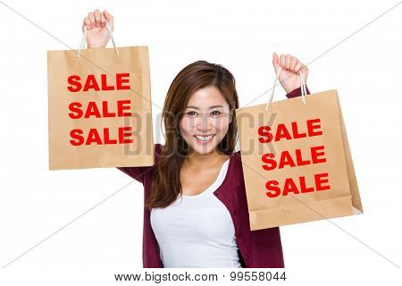 Asian woman raise up the shopping bag for showing three sale word