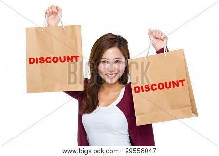 Asian woman raise up the shopping bag for showing a word discount