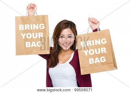 Asian woman raise up the shopping bag for showing bring your bag