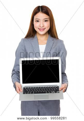 Young businesswoman show with the blank screen of laptop computer